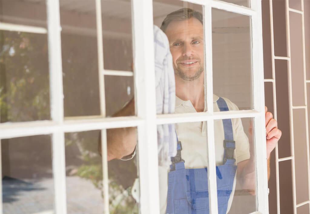 man cleaning window inside